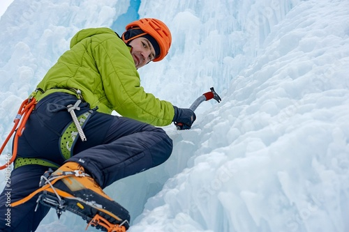 Alpinist man with ice tools axe in orange helmet climbing a large wall of ice Wallpaper Mural