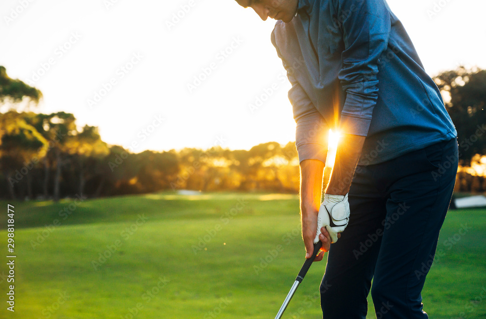 Fototapeta Male golf player teeing off golf ball from tee box to beautiful sunset