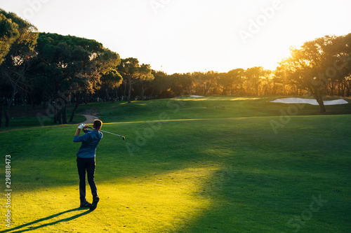 Male golf player teeing off golf ball from tee box to beautiful sunset Fototapete