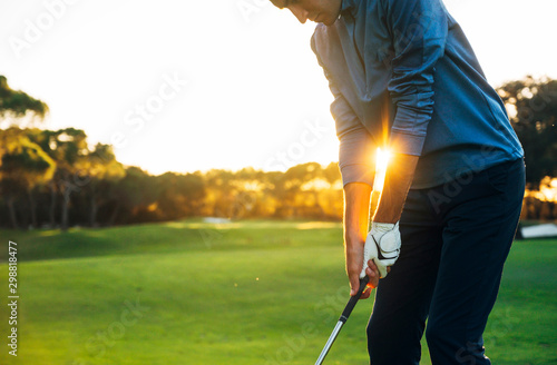 Fotomural Male golf player teeing off golf ball from tee box to beautiful sunset