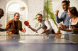 canvas print picture - Young people playing table tennis in workplace, having fun. Friends in casual clothes play ping pong together at sunny day. Concept of leisure activity, sport, friendship, teambuilding, teamwork.