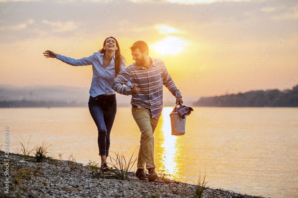 Fototapety, obrazy: Happy caucasian fashionable couple in love holding hands and walking on coast near river. Man holding picnic basket. In background is sunset.