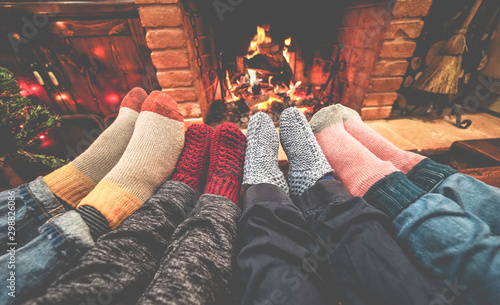 Legs view of happy family lying down next fire place wearing warm wool socks - W Fototapet