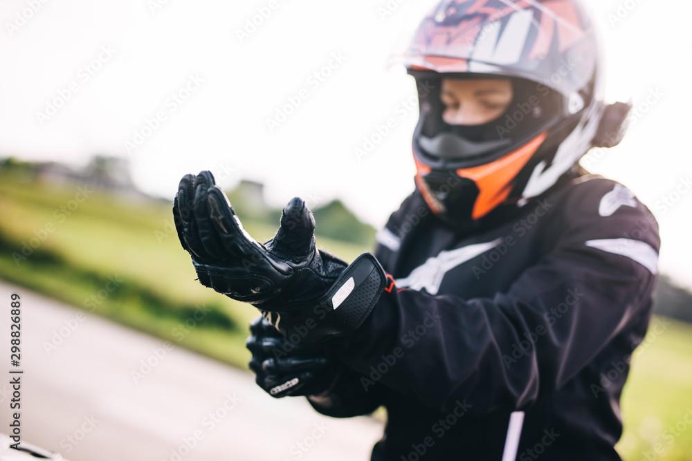 Fototapeta Woman preparing to drive a motorbike. Wearing gloves