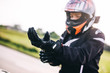 Leinwandbild Motiv Woman preparing to drive a motorbike. Wearing gloves