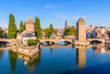 The Ponts Couverts, A Medieval Set Of Bridges And Towers On The River Ill At The Entrance Of The Petite France Historic Quarter In Strasbourg, France, And Notre-Dame Cathedral In The Distance.