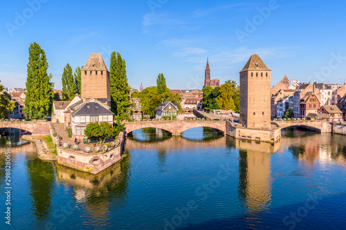 Stampa su Tela  The Ponts Couverts, a medieval set of bridges and towers on the river Ill at the entrance of the Petite France historic quarter in Strasbourg, France, and Notre-Dame cathedral in the distance