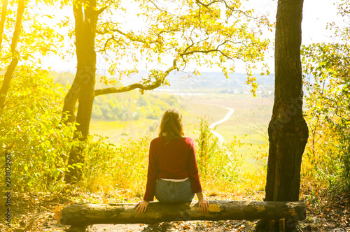 Foto auf Gartenposter Gelb Stylish hipster girl is sitting in forest. Happy woman enjoying autumn nature. Beautiful landscape. Lifestyle travel concept. Dark red sweater. Yellow leaves on trees. View from mountain hill.