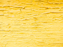 Wood Texture With Yellow Flaked Paint. Peeling Paint On Weathered Wood. Old Cracked Paint Pattern On Rusty Background. Chapped Paint On An Old Wooden Surface