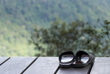 Slippers Are Placed On A Wooden Terrace With A Forest And Mountain Background.
