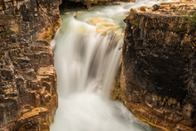 Smooth Milky Waters Of A Waterfall Squeezing Through A Narrow Rock Opening In Jasper National Park, Canada
