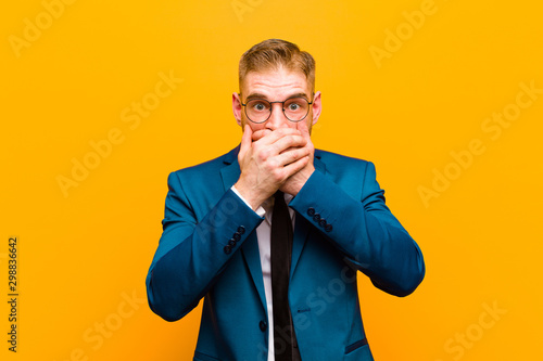 Photo  young red head businessman covering mouth with hands with a shocked, surprised e