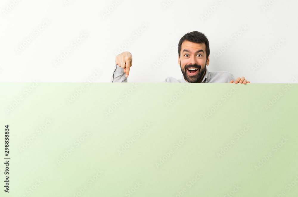 Fototapeta Young handsome man with beard holding a big green empty placard and pointing it