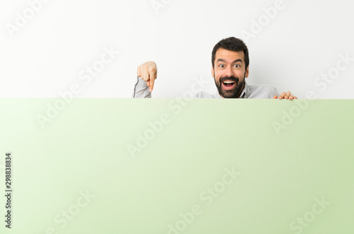 Young handsome man with beard holding a big green empty placard and pointing it - 298838834