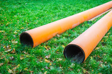 Two Water Pipes On Grass During Plumbing Repairs Under Construction