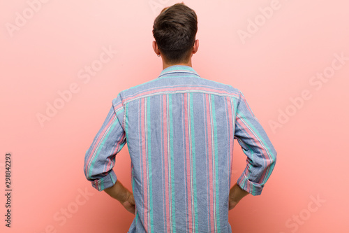 young man feeling confused or full or doubts and questions, wondering, with hands on hips, rear view against pink background