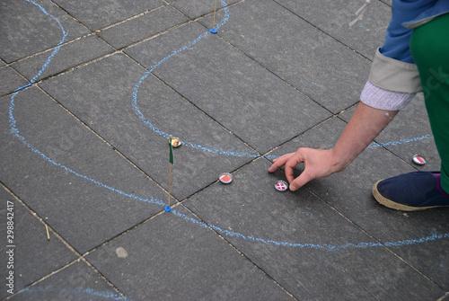 Fotografia  Dzieci grające w kapsle na chodniku