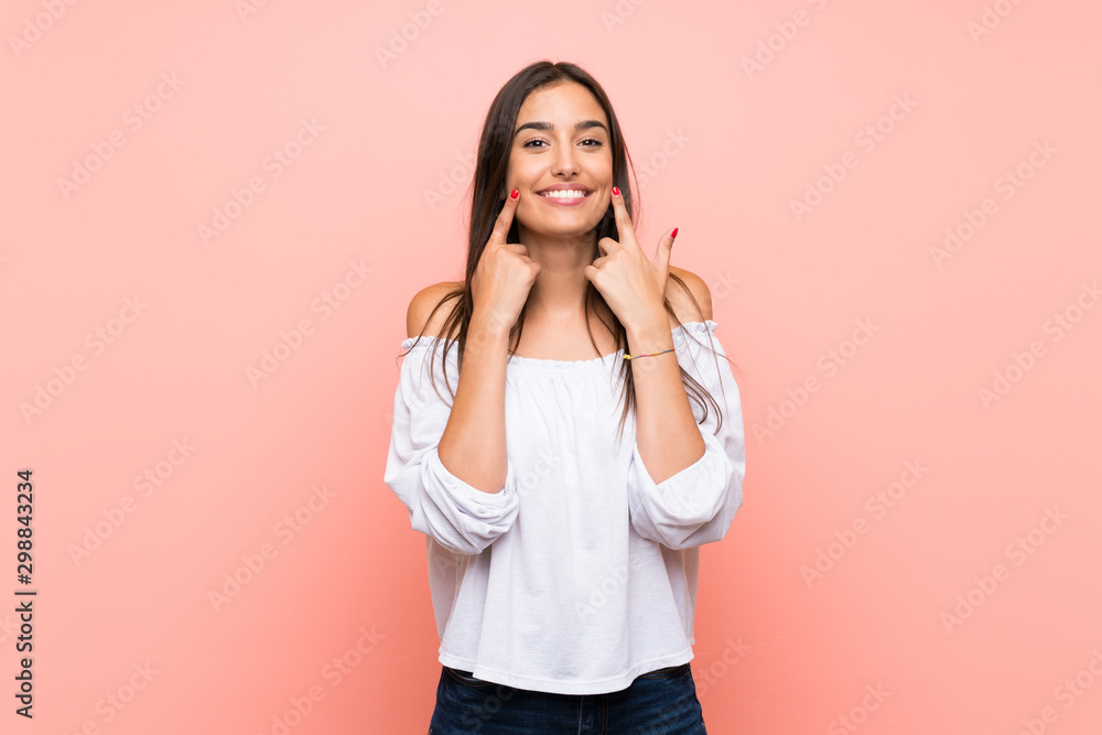 Fototapety, obrazy: Young woman over isolated pink background smiling with a happy and pleasant expression