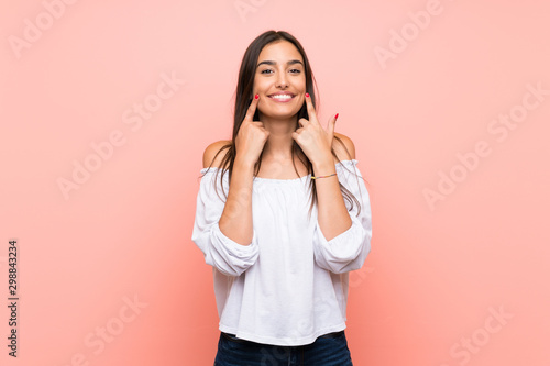 Fototapeta Young woman over isolated pink background smiling with a happy and pleasant expression obraz