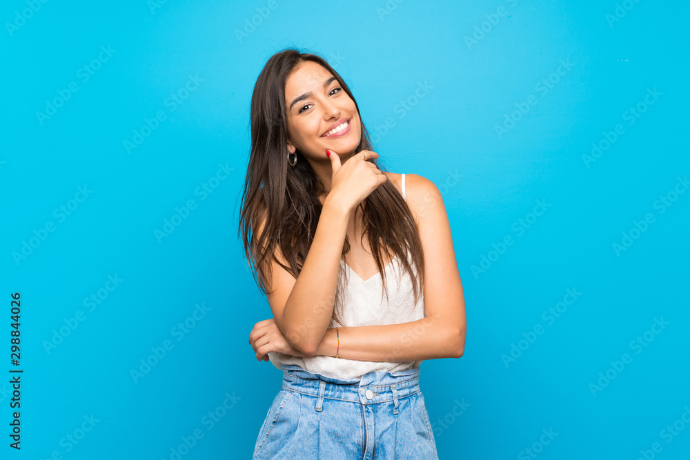 Fototapety, obrazy: Young woman over isolated blue background smiling
