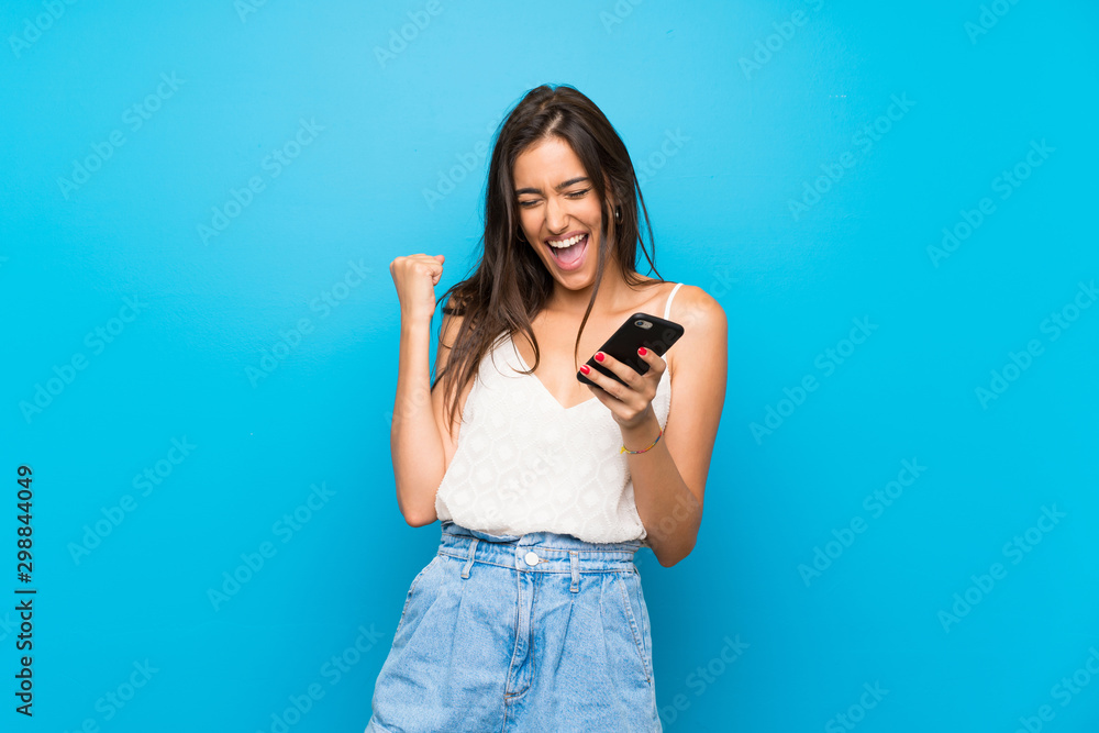 Fototapeta Young woman over isolated blue background with phone in victory position
