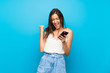 Young woman over isolated blue background with phone in victory position