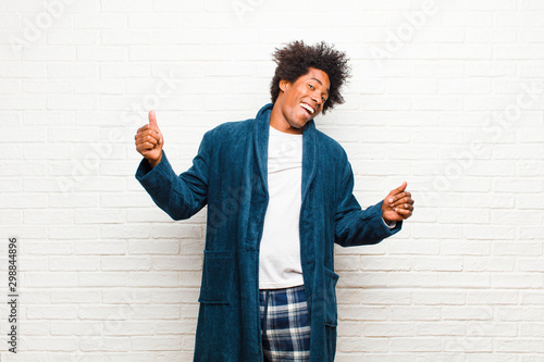 young black man wearing pajamas with gown smiling, feeling carefree, relaxed and happy, dancing and listening to music, having fun at a party against brick wall - 298844896