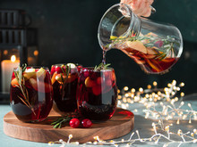 Female Hand Pours Winter Sangria In Glasses With Fruit Slice, Cranberry And Rosemary. Dark Christmas Holiday Background With Candle, Decoration Lighting Chain.