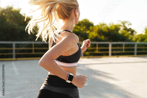 Foto Image of attractive fitness woman wearing tracksuit running outdoors