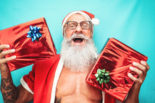 Happy Santa Claus Holding Christmas Present - Hipster Fit Senior Having Fun Celebrating X-mas Holidays - Elderly People And Traditional Lifestyle Culture
