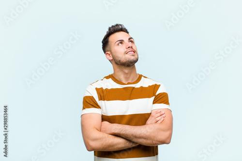 Valokuvatapetti young hispanic man feeling happy, proud and hopeful, wondering or thinking, look