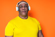 canvas print picture - elderly black man is listening to music on his headphones with an orange background