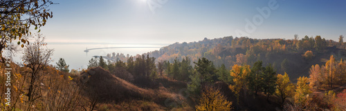 Steep shore of reservoir with trees in morning haze, panoramic