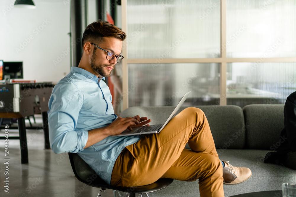 Fototapeta Young man typing on laptop