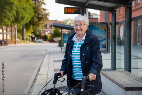 Fotografiet Very old senior woman waiting at the bus stop with walker