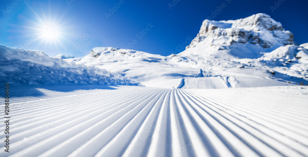 Fototapety, obrazy: New groomed ski piste or slope. Lines in snow with sunny mountains background. Winter skis concept.