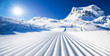 Leinwanddruck Bild - New groomed ski piste or slope. Lines in snow with sunny mountains background. Winter skis concept.