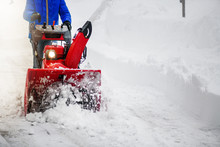 Man Clearing Or Removing Snow With A Snowblower On A Snowy Road Detail.