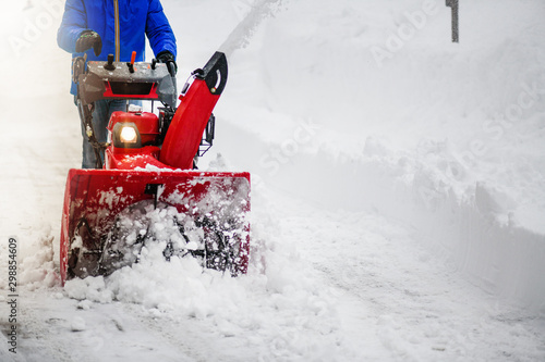 Man clearing or removing snow with a snowblower on a snowy road detail Wallpaper Mural