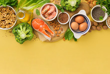 Omega 3 Food Sources And Omega 6 On Yellow Background Top View. Foods High In Fatty Acids Including Vegetables, Seafood, Nut And Seeds