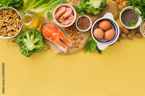 Fotografia  Omega 3 food sources and omega 6 on yellow background top view