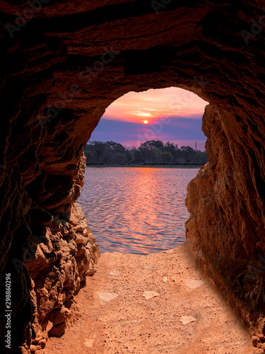 Foto auf Leinwand Braun View of a lake sunset from a stone tunnel
