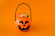 Leinwanddruck Bild - Orange plastic candy basket in the shape of a pumpkin jackolantern on a orange background. Place for your text, layout for advertising