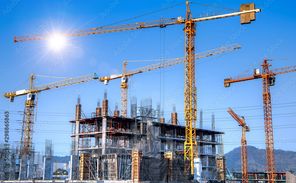 Fototapeta Workers are working on large construction sites and many cranes are working in the construction industry.