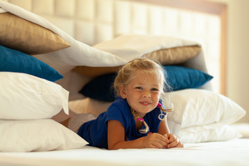 Little cute girl built impromptu fort (castle, house) out of pillows and blankets on bed. Children handmade tent lodge.