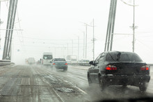 Cars Drive Along Road With Slush, Snowstorm. City Traffic In Snow Blizzard.
