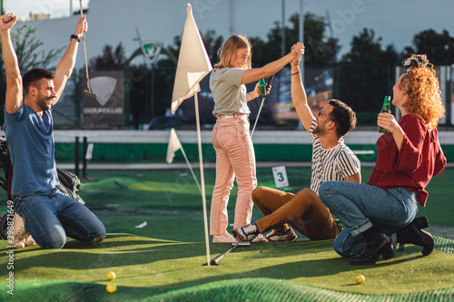 Group of smiling friends enjoying together playing mini golf in the city Canvas Print