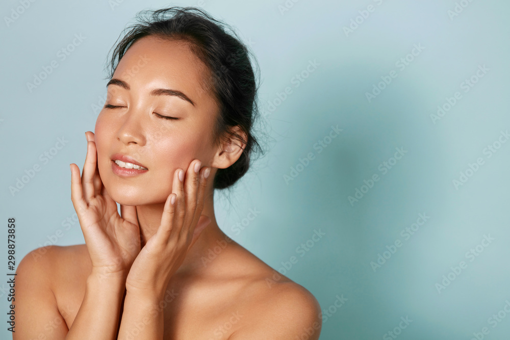 Fototapeta Skin care. Woman with beauty face and healthy facial skin portrait. Beautiful asian girl model with natural makeup touching glowing hydrated skin on blue background closeup. High quality image