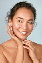 Face Skin Care. Woman Applying Cosmetic Cream On Clean Hydrated Skin Portrait. Beautiful Happy Smiling Asian Female Model With Natural Makeup Applying Facial Moisturizer, Beauty Product. High Quality
