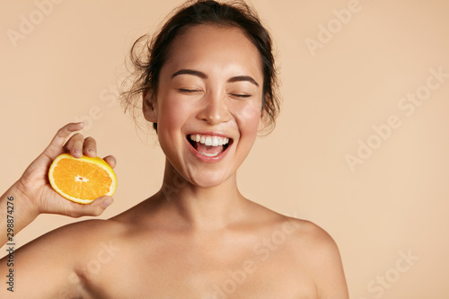 Fototapeta Beauty. Smiling woman with radiant face skin and orange portrait. Beautiful smiling asian girl model with natural makeup, healthy smile and glowing hydrated facial skin. Vitamin C cosmetics concept obraz